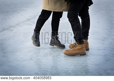 Women's And Men's Legs In Leather Boots On The Rink. A Man And A Woman Are Hugging. The Plot For Val