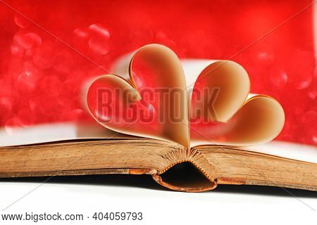 Pages of open book rolled in heart shape on glitter background, love reading, valentines day