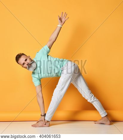 Mature Handsome Bearded Gray-haired Man In Sportswear Practices Yoga While Standing In An Elongated