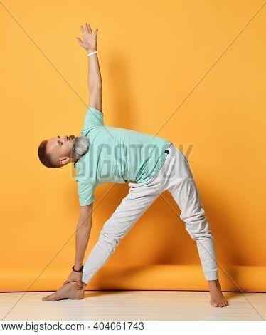 Mature Handsome Bearded Grey-haired Man In Sportswear Practicing Yoga Standing On Utthita Trikonasan