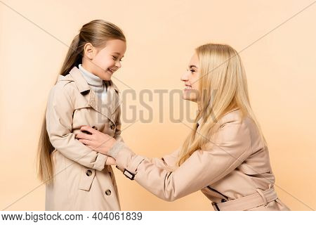 Cheerful Blonde Mother Tickling Happy Daughter Isolated On Beige