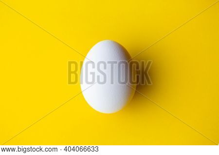 White Egg On A Yellow Background. Egg On A Yellow Background. White Egg With Shadow.easter Concept.b
