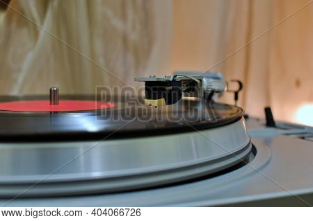 motion blurred of vinyl record disk, turntable head on motion blurred background of  vinyl record
