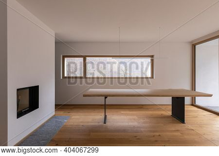 Modern house interior with white walls and parquet floors. Wooden table with design lamp, fireplace and window to the forest of the Swiss Alps.  Nobody inside