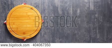 Pizza cutting board and cloth napkin on stone surface of table. Food recipe concept at tabletop or wall background texture with copy space. Flat lay of  panorama, panoramic top view