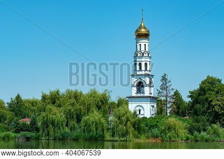 Landscape View Of Beautiful Belfry On The Riverside Between Lush Greens