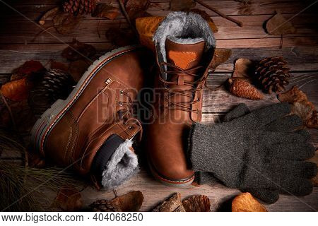 A Pair Of Winter Boots Along With Woolen Gloves