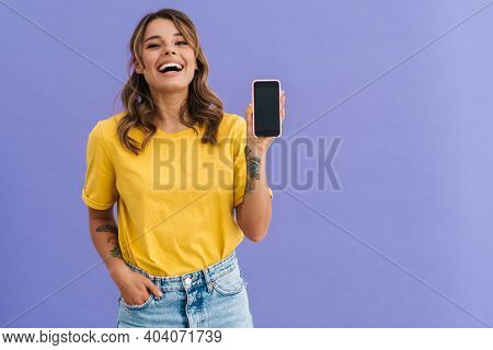 Smiling young woman showing blank screen smartphone isolated over blue background