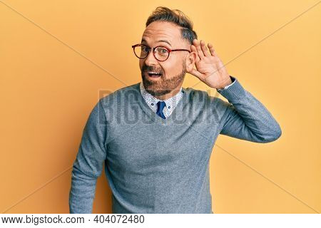 Handsome middle age man wearing glasses smiling with hand over ear listening and hearing to rumor or gossip. deafness concept.