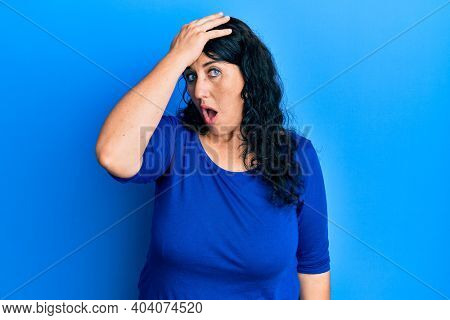 Plus size brunette woman wearing casual blue shirt surprised with hand on head for mistake, remember error. forgot, bad memory concept.