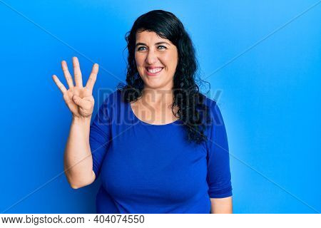 Plus size brunette woman wearing casual blue shirt showing and pointing up with fingers number four while smiling confident and happy.
