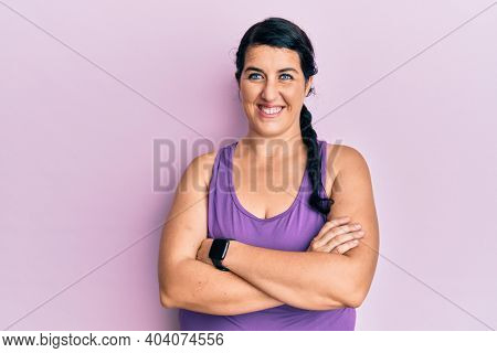 Plus size brunette woman wearing sportswear happy face smiling with crossed arms looking at the camera. positive person.