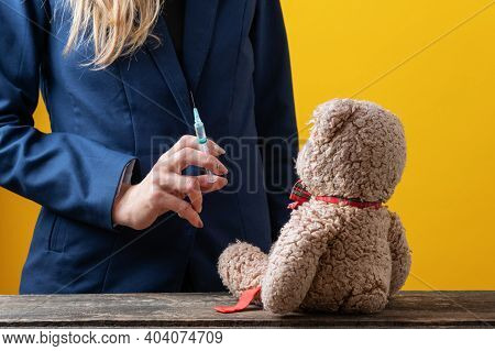 Woman In Business Jacket Holding Medical Syringe With Vaccine Or Medicine With A Teddy Bear Toy Sitt