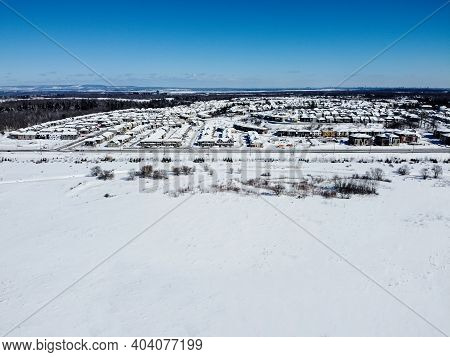 Aerial Of The Kanata Neighborhood In Winter. Suburbian Houses Next To A Large Area Covered With Snow