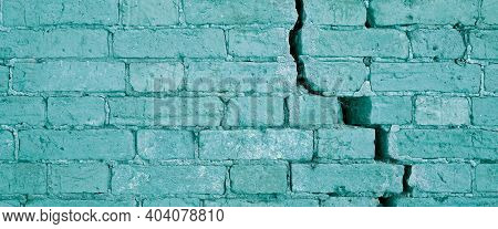 Light Blue Brick Wall With Crack Structure. Damaged Brickwork Surface Texture. Destroyed And Aged Ol