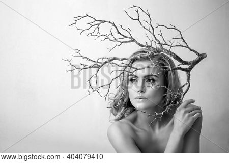Conceptual creative black and white portrait of woman with tree branch. ?irl is alone in nature. Ecology, preservation of planet.