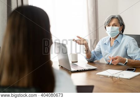Elder Senior Female Hr Manager Sitting At The Office, Wearing Face Mask, Training Young Female Worke
