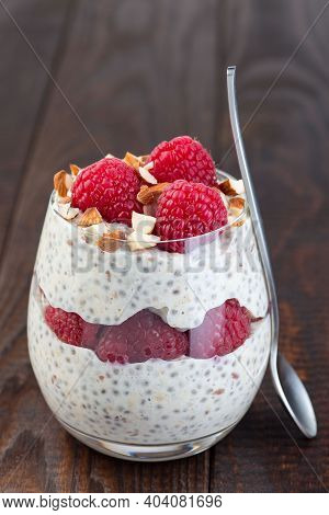 Overnight Oats With Chia And Flax Seeds, Garnished With Raspberry And Almond, On A Wooden Background