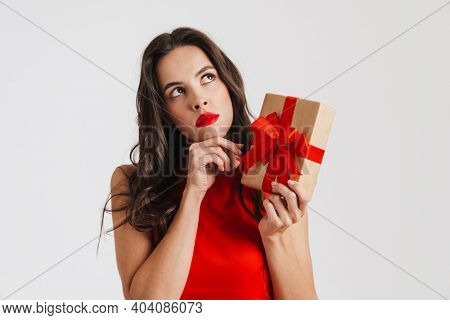 Perplexed beautiful brunette girl posing with gift box isolated over white background