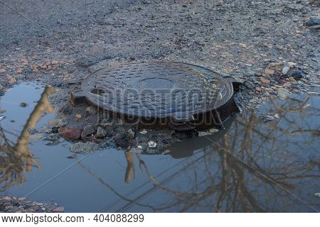 One Brown Iron Manhole On The Gray Asphalt Of The Road Near A Puddle Of Dirty Water