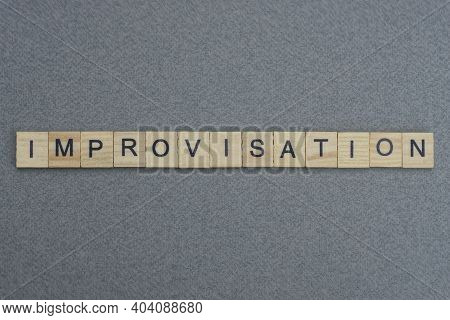 Text The Word Improvisation From Brown Wooden Small Letters With Black Font On An Gray Table