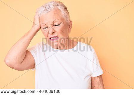 Senior beautiful woman with blue eyes and grey hair wearing classic white tshirt over yellow background confuse and wonder about question. uncertain with doubt, thinking with hand on head. pensive