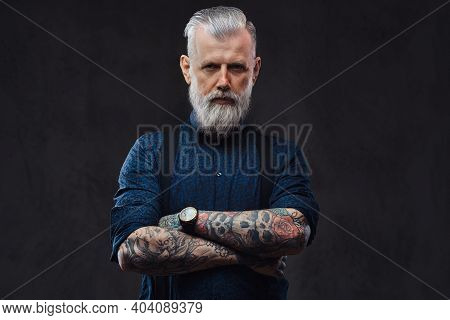 Brutal And Mature Man With In Gangster Style Poses In Dark Background With Crossed Arms.