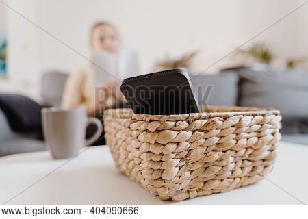 Millennial Girl At Home Refuse Using Phone And Reading A Book. Social Media Addiction. Waste Of Time