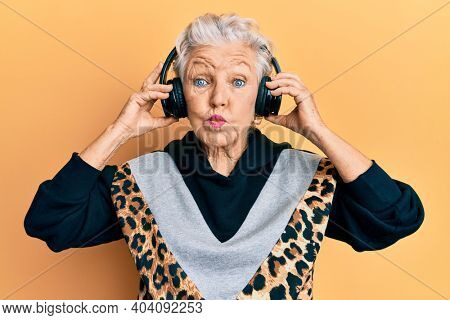Senior grey-haired woman listening to music using headphones puffing cheeks with funny face. mouth inflated with air, catching air.