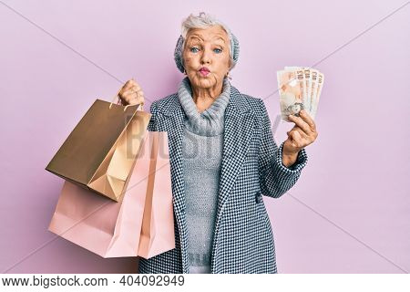 Senior grey-haired woman holding shopping bags and uk pounds banknotes puffing cheeks with funny face. mouth inflated with air, catching air.