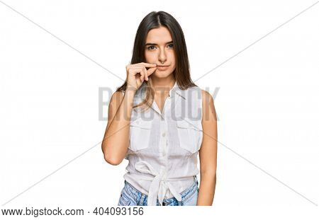 Young hispanic woman wearing casual clothes mouth and lips shut as zip with fingers. secret and silent, taboo talking
