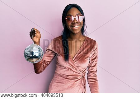 Young african american woman wearing sexy party dress holding disco ball looking positive and happy standing and smiling with a confident smile showing teeth