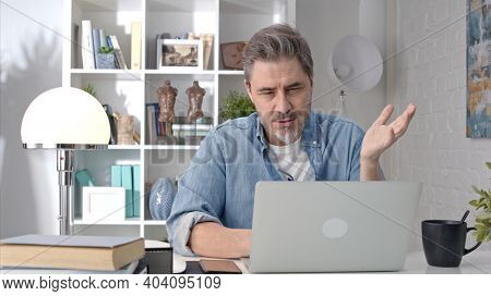 Older white man sitting at desk using laptop in home office. 50s businessman on video chat conference call and working from home.