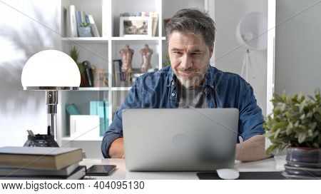 50s man working online with laptop computer at home sitting at desk, smiling. Home office, browsing internet, study room.