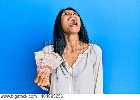 Young african american woman holding 10 colombian pesos banknotes angry and mad screaming frustrated and furious, shouting with anger. rage and aggressive concept.