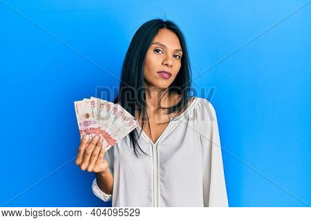 Young african american woman holding 10 colombian pesos banknotes looking sleepy and tired, exhausted for fatigue and hangover, lazy eyes in the morning.