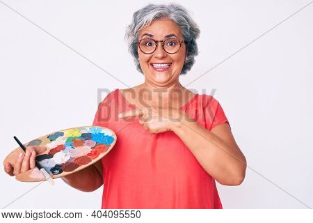 Senior hispanic grey- haired woman holding paintbrush and palette smiling happy pointing with hand and finger