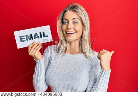 Beautiful blonde woman holding paper with email address pointing thumb up to the side smiling happy with open mouth