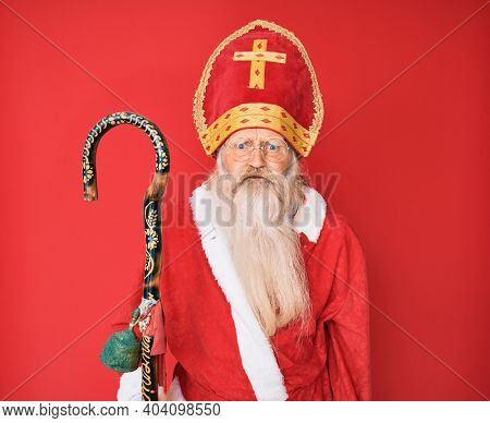 Old senior man with grey hair and long beard wearing traditional saint nicholas costume puffing cheeks with funny face. mouth inflated with air, crazy expression.