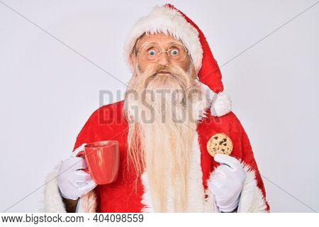 Old senior man with grey hair and long beard wearing santa claus costume eating cookies puffing cheeks with funny face. mouth inflated with air, catching air.