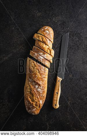 Crispy fresh baguettes. Sliced baguette on black table. Top view.