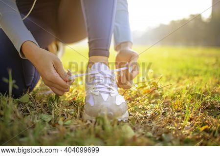 Female Runner Tying Her Shoes Preparing For A Jog Outside At Morning