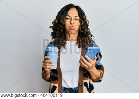 Middle age hispanic woman drinking a cup of coffee and looking at the smartphone screen puffing cheeks with funny face. mouth inflated with air, catching air.