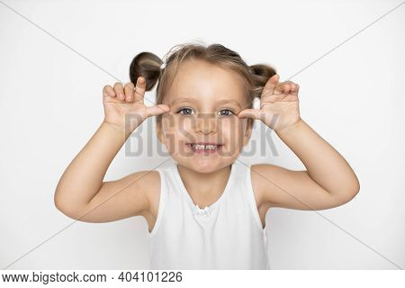 Little Cute Laughing Caucasian 3 Years Old Girl Makes Grimace With Her Hands And Face. Crazy Funny L