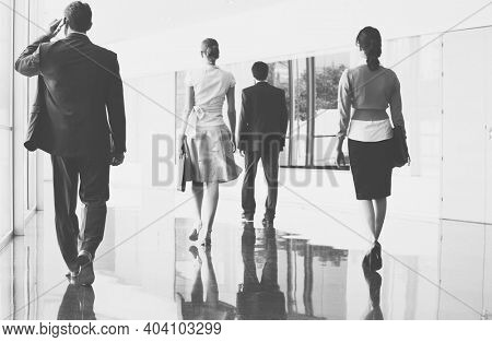 Black and white photo of business people walking on marble flooring in office
