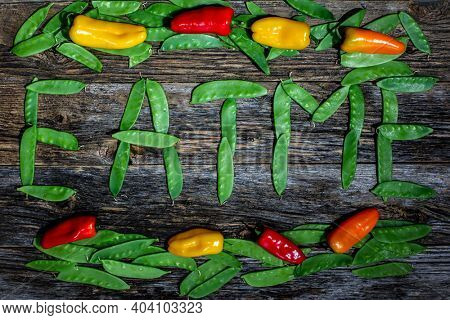 Snow peas text eat me with sweet peppers on rustic wooden background
