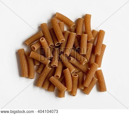 Raw Whole Grain Brown Pasta On A White Background. Wholemeal Pasta Made Of Durum Flour, Rich In Nutr