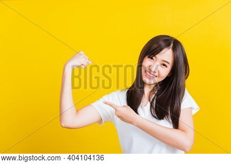 Portrait Asian Of Happy Beautiful Strong Young Woman Raises Arms Biceps Confident Showing Power And