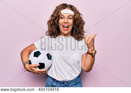 Middle age beautiful sporty woman playing soccer holding football bal over pink background pointing thumb up to the side smiling happy with open mouth