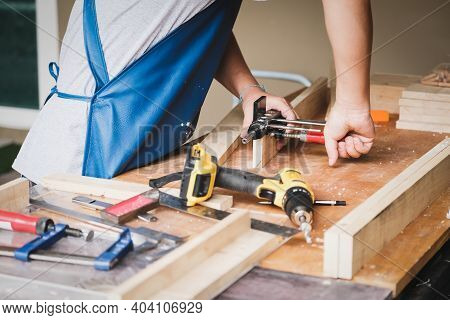 Woodworking Operators Are Using Woodworking Tools To Prepare A Drill, Drill Holes In Wood To Assembl
